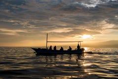Verbazende zonsopgang met silhouet van mensen in kleine boot in Lovin Stock Fotografie
