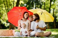 Verbergend van de zon onder grote rode en gele paraplu'smoeder, zitten de vader en hun kinderen op de deken en royalty-vrije stock afbeeldingen