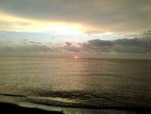 verbergende zonsondergang bij het strand Stock Foto's