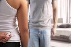 Verbergende zwangerschapstest van echtgenoot Stock Foto