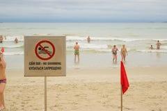 Verbiedend teken Geen Zwemmende en rode vlag bij een strand stock afbeelding