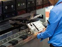 Verbiegende Blechtafel des Betreibers durch verbiegende Maschine des Blattes lizenzfreies stockfoto