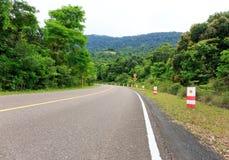 Verbiegende Straße zur Spitze eines Berges mit grünen Bäumen und Traff Lizenzfreies Stockbild