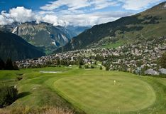 Verbier and golf. Golf course with green grass looking over the town of verbier, swiss Royalty Free Stock Photos