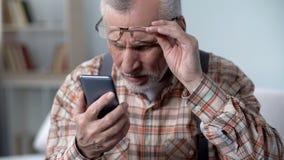 Verbijsterde oude mens die cellphone, nieuwe technologie bekijken ingewikkeld voor bejaarden royalty-vrije stock afbeeldingen
