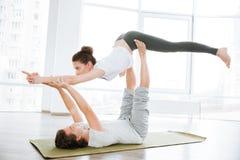 Verbinden Sie übendes acro Yoga auf grüner Matte im Studio zusammen Lizenzfreie Stockbilder