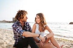 Verbinden Sie auf dem Strand zusammen sitzen und sprechen Lizenzfreie Stockfotografie