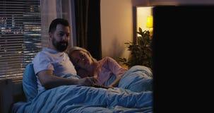 Verbinden Sie aufpassendes Fernsehen vom Bett stock footage