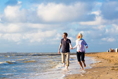 Verbinden Sie Betrieb durch Sand und Wellen am Strand Stockbild