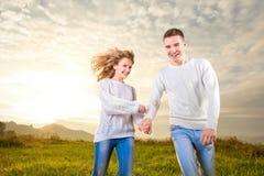 Verbinden Sie Betrieb und Lachen und Händchenhalten unter dem Himmel lizenzfreie stockbilder