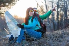 Verbinden Sie das Betrachten der Karte beim Sitzen auf Gras Stockfotos