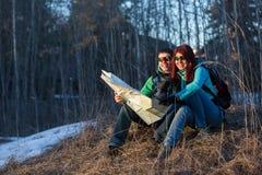 Verbinden Sie das Betrachten der Karte beim Sitzen auf Gras Stockfotografie