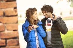 Verbinden Sie das Betrachten eines Handys und der hörenden Musik lizenzfreie stockbilder