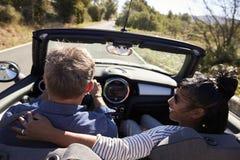 Verbinden Sie das Fahren in Auto, Frauenblicke auf ihren Partner, hintere Ansicht Stockfotos