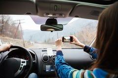 Verbinden Sie das Fahren in Auto und das Machen von Fotos mit Smartphone Lizenzfreie Stockfotografie