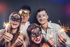 Verbinden Sie das Feiern neues Jahr ` s des trinkenden Champagners Vorabends und das Beleuchten herauf Wunderkerzen auf Maskerade lizenzfreies stockfoto