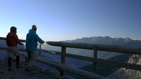 Verbinden Sie das Gehen zum hölzernen Balkon und das Betrachten des Bergblicks bei dem Sonnenaufgang, der oben auf den Alpen hoch stock video