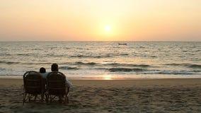 Verbinden Sie das Genießen des Sonnenuntergangs und in den Lehnsesseln nahe der Ozeanküstenlinie sitzen stock video footage