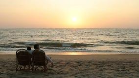 Verbinden Sie das Genießen des Sonnenuntergangs und in den Lehnsesseln nahe der Ozeanküstenlinie sitzen stock video