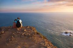 Verbinden Sie das Genießen eines romantischen Sonnenuntergangs und des Ozeans Stockbild