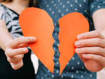 Verbinden Sie das Halten einer halben Herzform, die auseinander bricht - scheiden Sie sich, spli lizenzfreie stockbilder