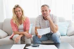 Verbinden Sie das Handeln ihrer Konten, die in einer Couch gesessen werden Stockfotos