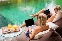 Verbinden Sie das Kühlen durch das Pool und das Arbeiten an Computern lizenzfreies stockfoto