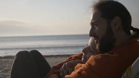 Verbinden Sie das Lügen, das auf dem aufpassenden Sonnenaufgang des Aufenthaltsraums auf dem Strand früh morgens bedeckt mit Deck stock footage