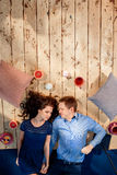 Verbinden Sie das Lügen auf Holzfußboden mit Kissen und Bonbons Stockfotografie