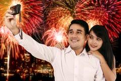 Verbinden Sie das Machen von selfie Foto mit dem Feuerwerkshintergrund Stockfotos
