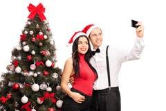 Verbinden Sie das Nehmen eines selfie durch einen Weihnachtsbaum Stockfotografie