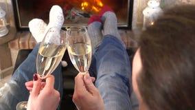 Verbinden Sie das Rösten von Heizungsfüßen des Champagners zusammen nahe Kamin stock video