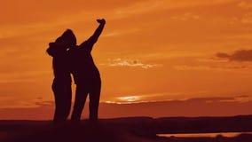 Verbinden Sie das Schattenbild, das draußen selfie tut Mann und Mädchen von den besten Freunden, die selfie während des Sonnenunt stock footage