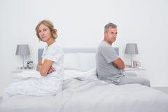 Verbinden Sie das Sitzen auf den verschiedenen Seiten des Betts sprechend nicht nach argum Lizenzfreies Stockbild