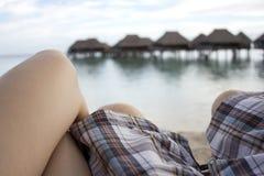 Verbinden Sie das Sitzen auf der Hängematte, die über den Strand- und overwaterhütten schaut Lizenzfreie Stockfotografie