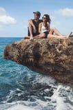 Verbinden Sie das Sitzen auf einem Felsen und das Betrachten der Ansicht Lizenzfreie Stockbilder