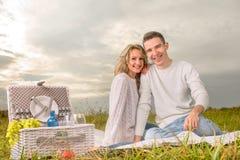 Verbinden Sie das Sitzen auf einem Picknick unter dem weißen Himmel stockbilder
