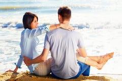 Verbinden Sie das Sitzen auf Sand am Strand, der das Meer schaut stockbild