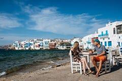Verbinden Sie das Sitzen auf Stühlen am Strand, Händchenhalten Stockfotos