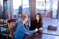 Verbinden Sie das Sitzen im Luncheonettehändchenhalten und die neue Diskussion Lizenzfreie Stockbilder