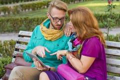 Verbinden Sie das Sitzen im Park, in Mann und in Frau, die Tablette betrachten lizenzfreie stockbilder
