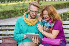 Verbinden Sie das Sitzen im Park, in Mann und in Frau, die Tablette betrachten lizenzfreies stockbild