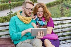 Verbinden Sie das Sitzen im Park, in Mann und in Frau, die Tablette betrachten stockfotos