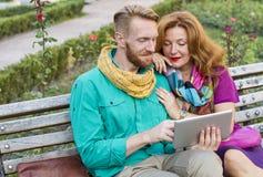 Verbinden Sie das Sitzen im Park, in Mann und in Frau, die Tablette betrachten lizenzfreie stockfotografie