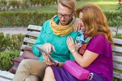Verbinden Sie das Sitzen im Park, in Mann und in Frau, die Tablette betrachten stockbilder
