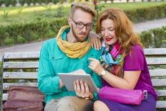 Verbinden Sie das Sitzen im Park, in Mann und in Frau, die Tablette betrachten stockfoto