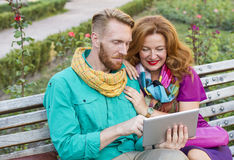 Verbinden Sie das Sitzen im Park, in Mann und in Frau, die Tablette betrachten stockfotografie