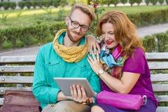Verbinden Sie das Sitzen im Park, in Mann und in Frau, die Tablette betrachten stockbild