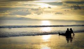 Verbinden Sie das Sitzen, schönen goldenen Sonnenuntergang genießend auf einem Strand lizenzfreie stockfotografie