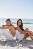 Verbinden Sie das Sitzen zurück zu Rückseite auf dem Sand, der an der Kamera lächelt Lizenzfreies Stockbild